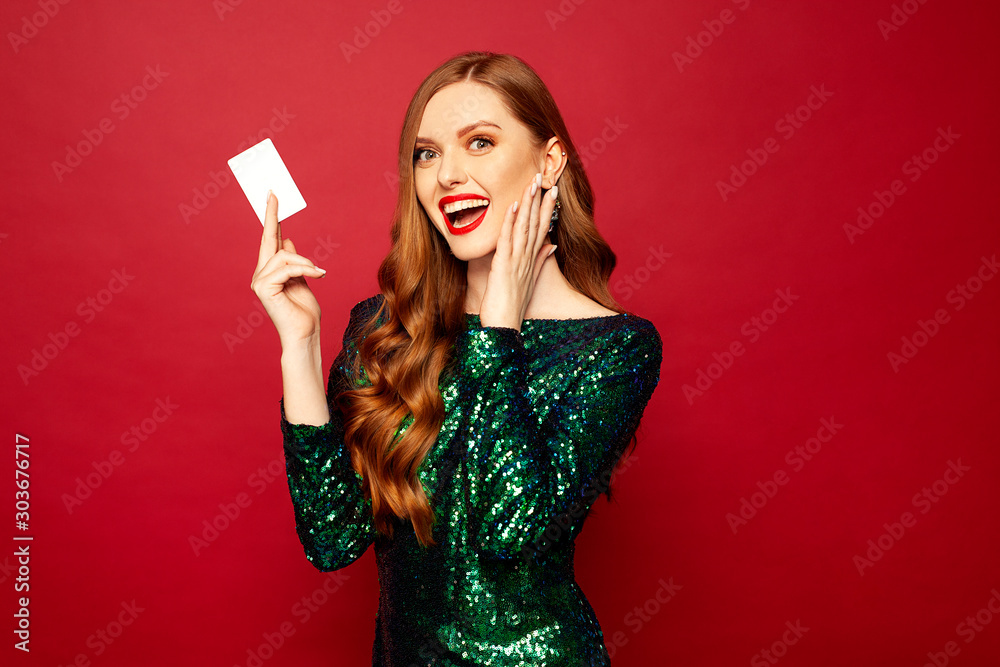 Fototapeta beautiful red-haired model stands on a red background and smiles a beautiful smile in brilliant dress, a card in hands , merry christmas and happy new year