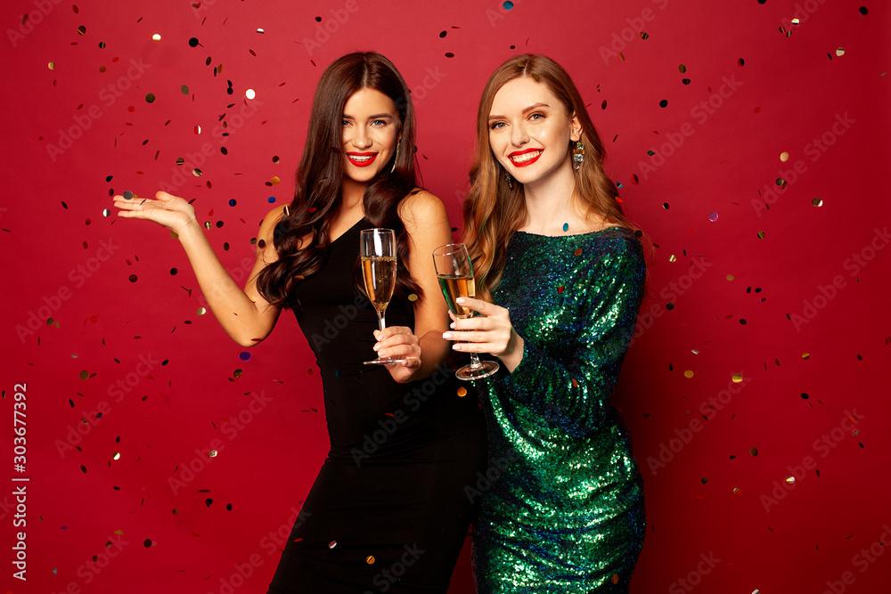 dwie piękne modelki, ruda i brunetka w noworocznych sukienkach, bawiących się i uśmiechających się z kieliszkami szampana, konfetti latającymi po czerwonym tle. Nowy rok lub zdjęcie świąteczne