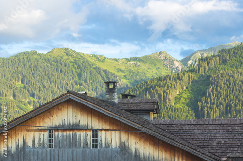 Foto auf Leinwand Olivgrun A small town at the foot of the mountains. Austrian village in a valley between the mountains. Rural landscape. Wooden roofs of houses. View of the Alps from the village. House in the mountains.