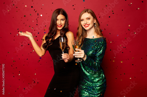 Obraz  two beautiful models, a redhead and a brunette in New Year's dresses, having fun and smiling with glasses of champagne, confetti flying around on a red background. New Year or Christmas photo - fototapety do salonu
