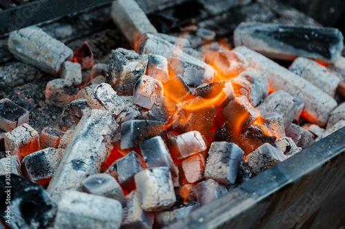 Brasas de carbón ardiendo con llamas para hacer comida parrillada, barbacoa.