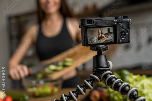 Pinturas sobre lienzo  Cheerful woman cooking fresh salad in kitchen and recording video lesson for fol