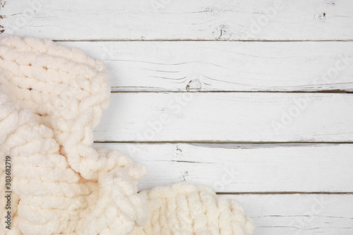 Obraz Cozy knitted thick wool blanket. Corner border top view on a white wood background with copy space. Cream color. - fototapety do salonu
