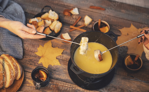 Top view friends cooking Swiss fondue assorted cheeses dinner on fire, hands hol Wallpaper Mural