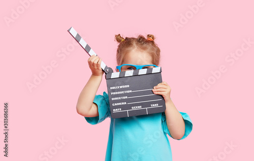 Foto  Funny smiling child girl in cinema glasses hold film making clapperboard isolated on pink background
