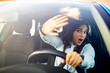 Young terrified woman driving and having a car accident. Mid adult woman driving and looking scared and surprised at the road in front of her. Woman in Car Crash