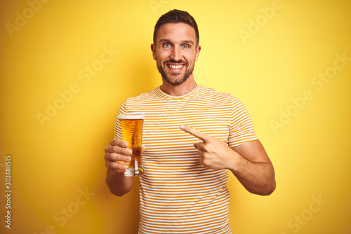 Obraz na plátně Young handsome man drinking a pint glass of beer over isolated yellow background