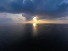 Morning Sunrise With Penetrating Sun Rays Through Black Rain Storm Clouds Over The Ocean Sea