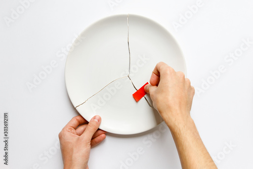 Fotomural  Top view of man hands holding a broken white plate, glues parts with red tape