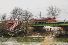 Overview Of A Train Wreck, Which Fell From A Bridge Almost Into A River. Scattered Derailed Train