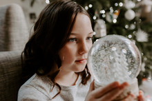 Girl Sitting By A Christmas Tr...