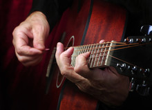 Playing An Acoustic Guitar. Guitarist Hands And Guitar Close Up.