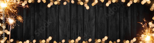 Fotografia  Silvester background banner panorama long- sparklers and boheh lights on rustic