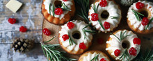 Christmas Muffins With Rosemary, White Icing And Red Berries. Elegant Holiday Cakes. Christmas Composition. Selective Focus. Macro.