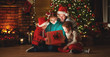 canvas print picture Merry Christmas! happy family mother father and children with magic gift near tree   at home.