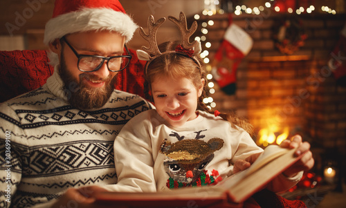 Obraz Christmas Eve. family father and child reading magic book at home . - fototapety do salonu