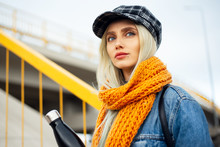 Portrait Of Young Blonde Teenager Girl, Wearing Blue Denim Jacket, With Orange Scarf And Plaid Cap, Holding A Black Steel Thermo Eco Water Bottle.