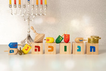 """Concept Of Of Jewish Religious Holiday Hanukkah With Hanukkah Chandellier (menorah) Wooden Spinning Top Toys (dreidel), Cubes Saying """"hanukkah"""" In Hebrew And Chocolate Coins"""