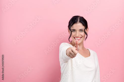 Obraz na plátně  Young woman giving thumb up on a pink background