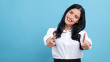 Young Woman Giving Thumbs Up On A Blue Background