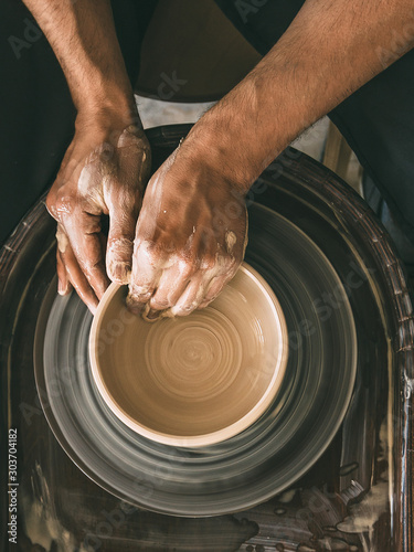 Fotografía Pottery workshop Top view Man is sculpting a bowl behind a rotating potter's whe