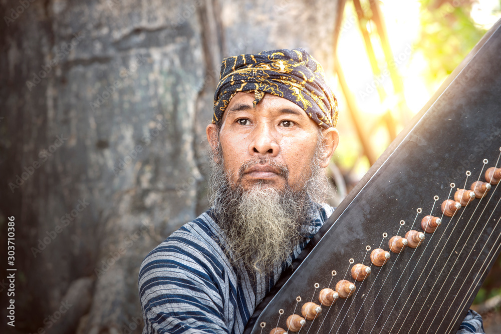 Fototapeta Asian old man holding kecapi with tree background