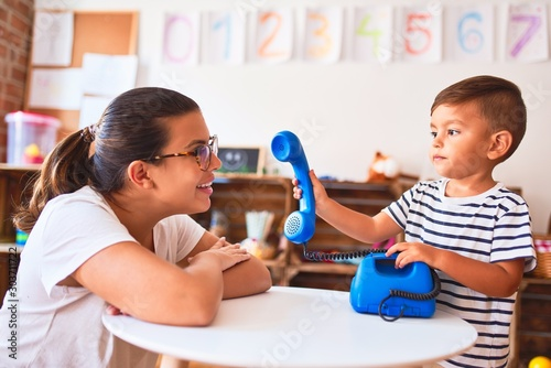 Fotografía  Beautiful teacher and toddler boy playing with vintage blue phone at kindergarte