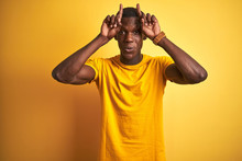 Young African American Man Wearing Casual T-shirt Standing Over Isolated Yellow Background Doing Funny Gesture With Finger Over Head As Bull Horns