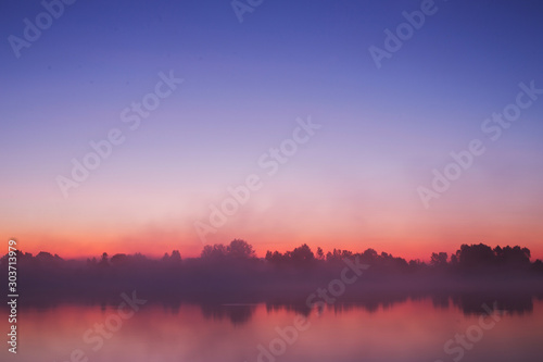 Obraz Mist over river. Nature background. Morning sunrise. Beautiful summer foggy landscape. Dusk over lake. Misty dawn. Picturesque sunriseVery dense fog. Dawn in morning. Picturesque orange sunset. - fototapety do salonu