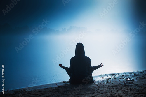 Silhouette of a man in darkness. Yoga meditation. Lotus position. Silhouette of man in hood. Dark shadow. Meditation in lotus pose. Yoga for mental health. Life concept. Relaxation on morning nature