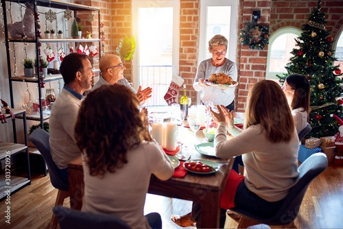 Obraz Family and friends dining at home celebrating christmas eve with traditional food and decoration, showing proud turkey cooking - fototapety do salonu