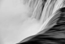 Grayscale High Angle Shot Of The Foamy Water Of A Waterfall