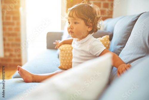 Canvastavla  Beautiful toddler child girl wearing white t-shirt sitting on the sofa