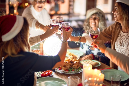 Beautiful group of women smiling happy and confident. Eating roasted turkey and toasting with cup of wine celebrating christmas at home - 303728746