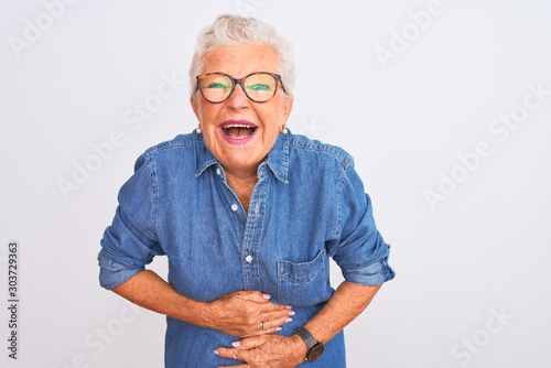 Fototapeta Senior grey-haired woman wearing denim shirt and glasses over isolated white background smiling and laughing hard out loud because funny crazy joke with hands on body