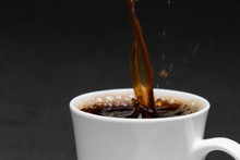 Close-up Pouring Hot Black Coffee Into A White Cup, Fresh Coffee, Black Background