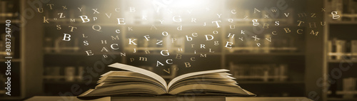 Imagine opening an old book blurred with magic power on the table and the English alphabet floating above the book with magic light as a beautiful background design Canvas Print