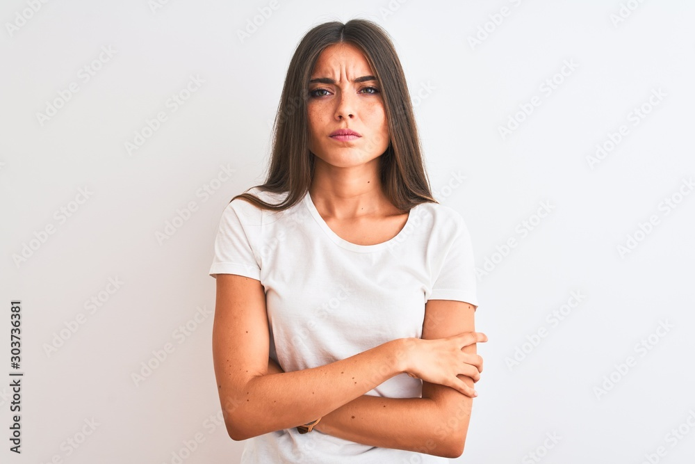 Fototapeta Young beautiful woman wearing casual t-shirt standing over isolated white background skeptic and nervous, disapproving expression on face with crossed arms. Negative person.