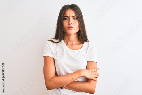 Fotografiet  Young beautiful woman wearing casual t-shirt standing over isolated white background skeptic and nervous, disapproving expression on face with crossed arms