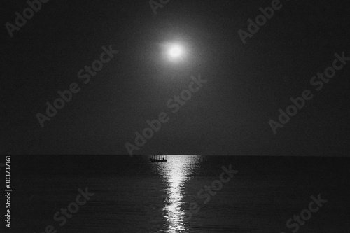 Grayscale shot of a boat in the calm sea with the reflection of the moon at night