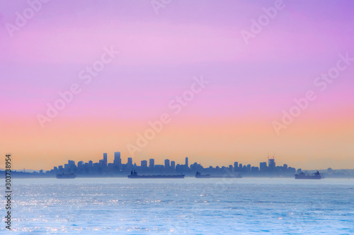 Foto op Plexiglas Purper Panorama view of cityscape with colorful sky, ocean and break-bulk carrier