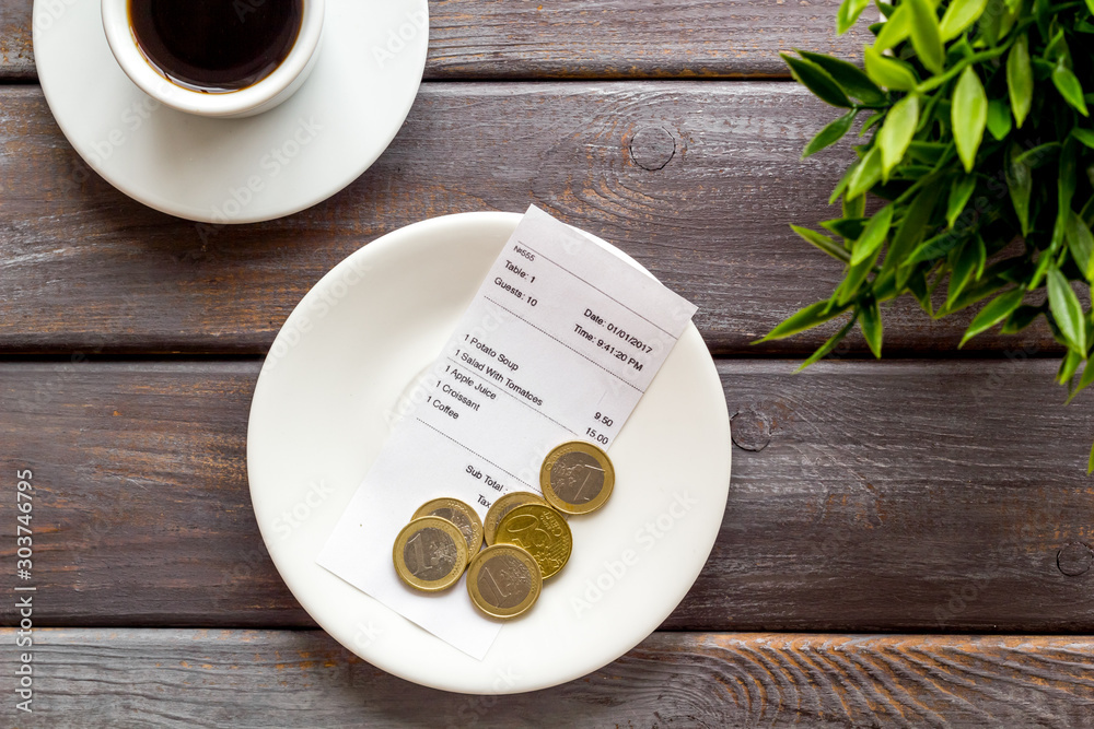 Fototapety, obrazy: Pay restaurant bill by cash. Reciept and coins on plate on dark wooden background top view