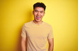 Young asian chinese man wearing t-shirt standing over isolated yellow background sticking tongue out happy with funny expression. Emotion concept.