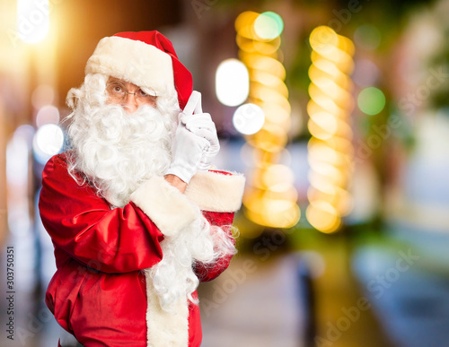 Fotografía  Middle age handsome man wearing Santa Claus costume and beard standing Holding s