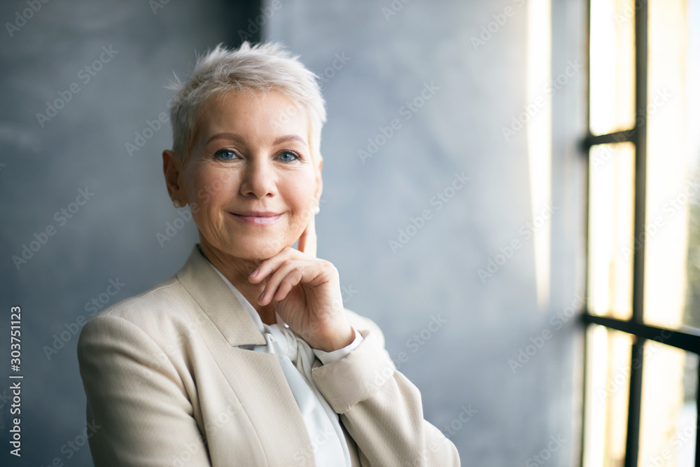 Fototapeta Elegant middle aged businesswoman with stylish pixie hair standing by window in office, touching face, thinking about business issues, looking at camera with confident smile. Success, career and job