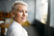 Close Up Portrait Of Attractive Mature Caucasian Woman With Blonde Pixie Haircut And Wrinkles Looking At Camera With Confident Smile While Working In Her Office. Business, Work, Job And Profession