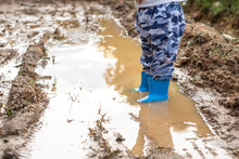 Foot Of Little Baby Wearing Blue Booty Walking Through Puddles Water In The Raining Season.