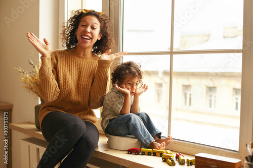 Indoor shot of cheerful charming young mother and cute barefooted little son sitting together on windowsill on rainy day, playing seek and hide, singing and dancing, having happy overjoyed looks - 303751375