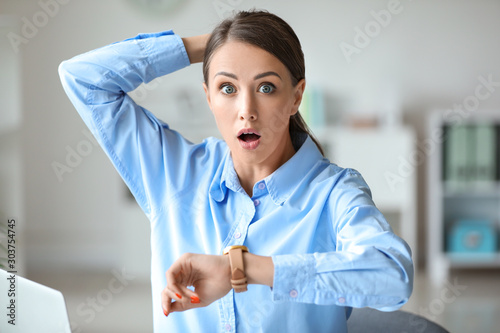 Stressed young woman trying to meet deadline in office Canvas Print