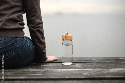 Fotografia  glass reusable bottle for water, stands on a wooden pier against the background